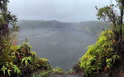 Looking into a volcanic crater, it's foggy.