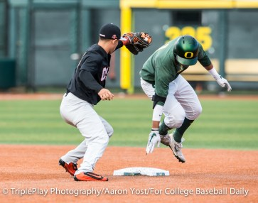 Oregon 's Kyle Kasser leaps back toward second after sliding past the bag while OSU second baseman Nick Madrigal tries to make the tag during the first inning of Thursday's Civil War game at PK Park.
