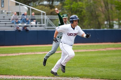 Friday, May 12, 2017; Storrs, CT; Connecticut Huskies first baseman Tyler Gnesda (25) runs to first base after bunting South Florida Bulls pitcher Phoenix Sanders (45) attempts to throw him out at first base during the Huskies 2-1 victory over the Bulls.