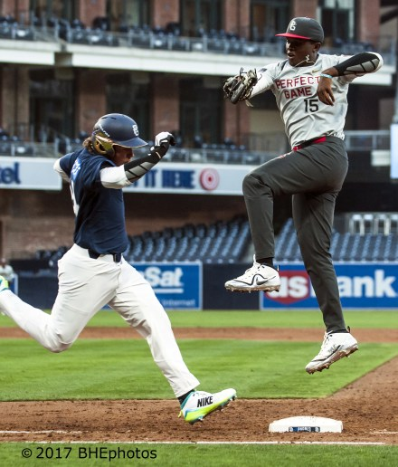 John Malcom makes a leaping save on the throw as Nicholas Northcut reaches first safely 2017 Perfect Game All American Game - Photo By David Cohen, BHEphotos