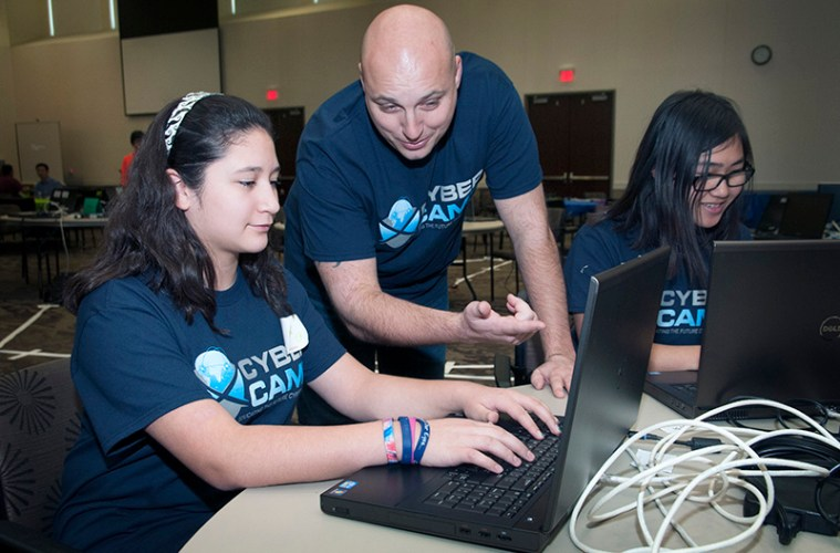 Students and professors work at the cyber security camp.