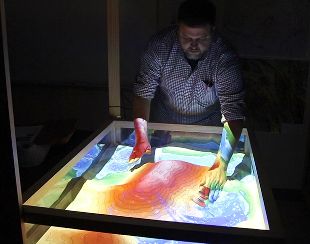 Neal Alexandrowicz, a geology professor at the Spring Creek Campus, manipulates the sand in the Augmented Reality Sandbox.