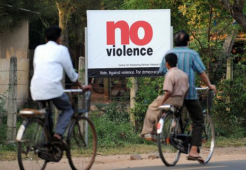 Sri Lankan cyclists pass an election pos
