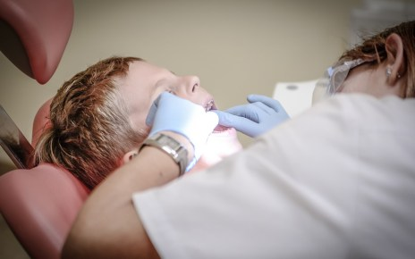 dentist doing dental care to boy