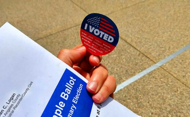 """A hand with """"I voted"""" sticker"""