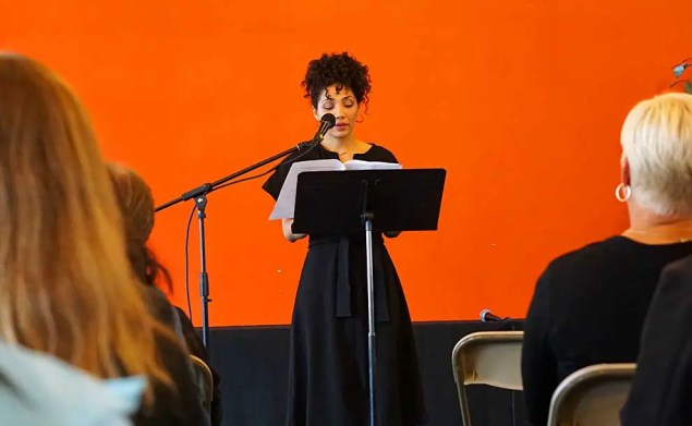 A person dressed in a black dress is reading an essay in front of an orange colored wall