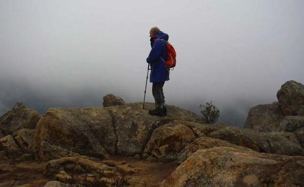 A standing on top of a summit sorrounded by mist