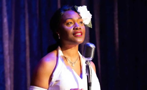 Actress Deidrie Henry wearing a large white rose on her hair and a white dress while standing in front of a microphone