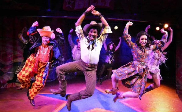 An African American coboy jumping in the air with a femae dressed in purple outfit behind him and a Cowboy clown to his left, all jumping in the air smiling