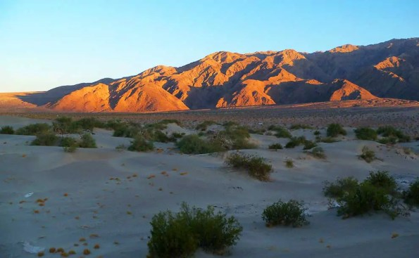 desert at sunset with sun rawy on the mountains