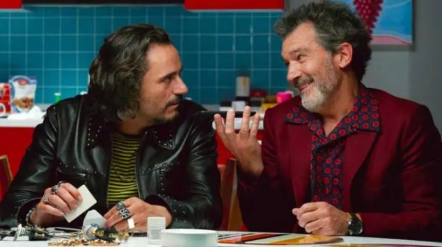 A guy with a beard wearing a burgundy shirt talks to a guy with a leather jacket at a counter