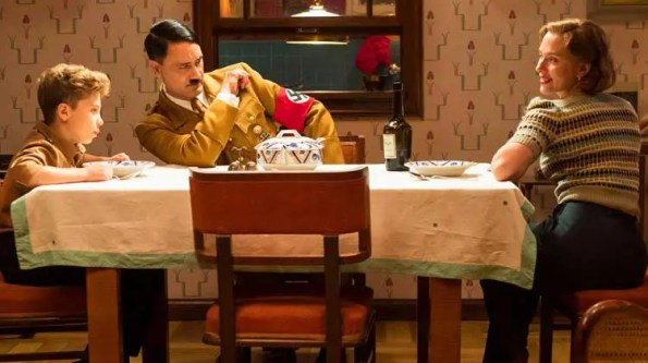 a man dressed as Hitler with a boy next to him and a mom on the other side of the dinner table