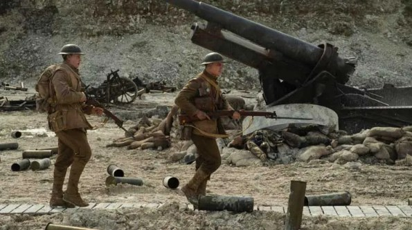 two soldiers pass a destroyed tanker