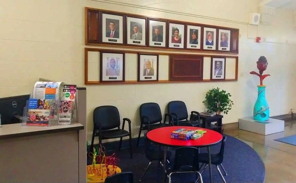A table and photos of the school board on the wall