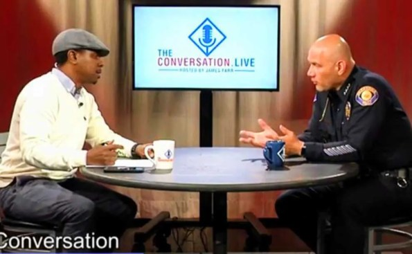 An African American person interviweing a chief of police