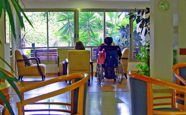 a person in awheelchair and a woman on a sofa looking out through a window