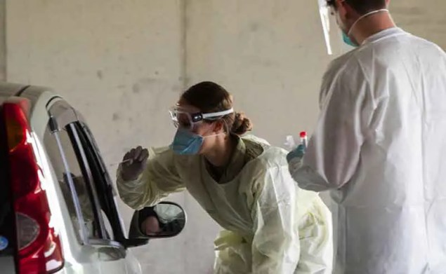 A woman with mask checks people inside a car