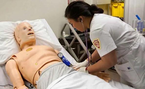 A student nurse tending to a dummy patient