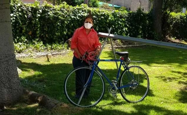 Woman holding a bike in a garden