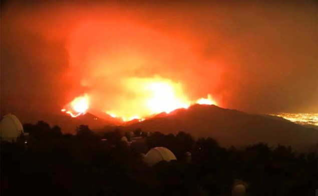 flames raging at night with hills in silhouette
