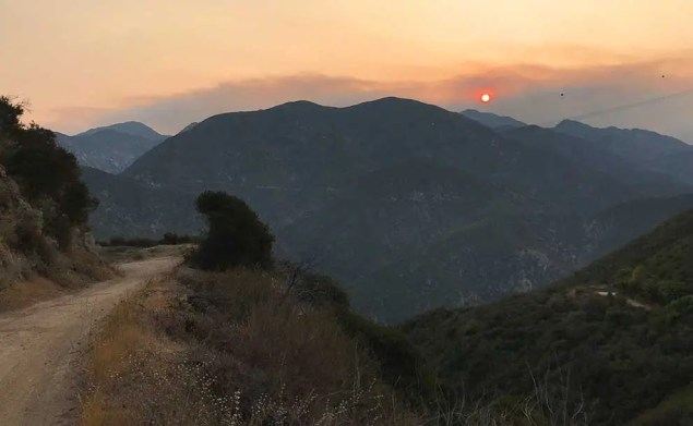 a trail to the left and hills. Sun is muted with dark orange colors