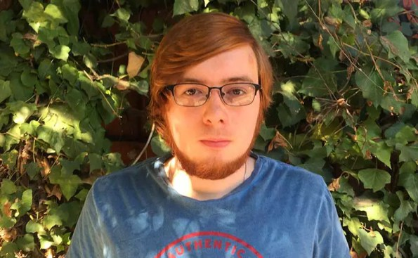 a red haired person with blue t-shit and glasses