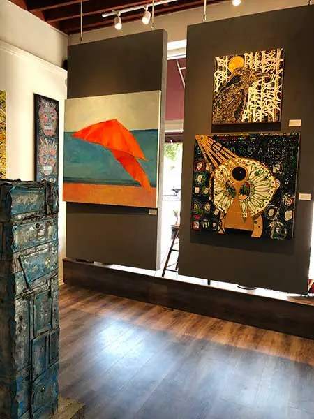paintings adorn the walls of a gallery