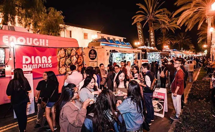 people congregating by food trucks