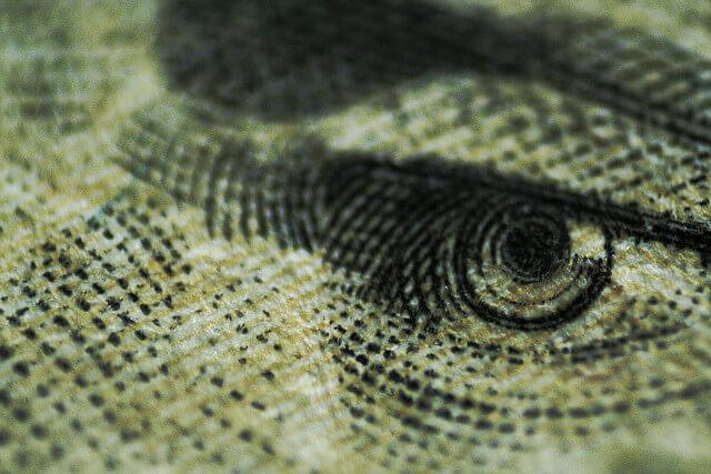 A closeup of an eye from a dollar bill.
