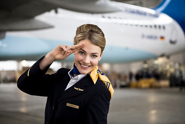 A pilot salutes before her airplane takes off.