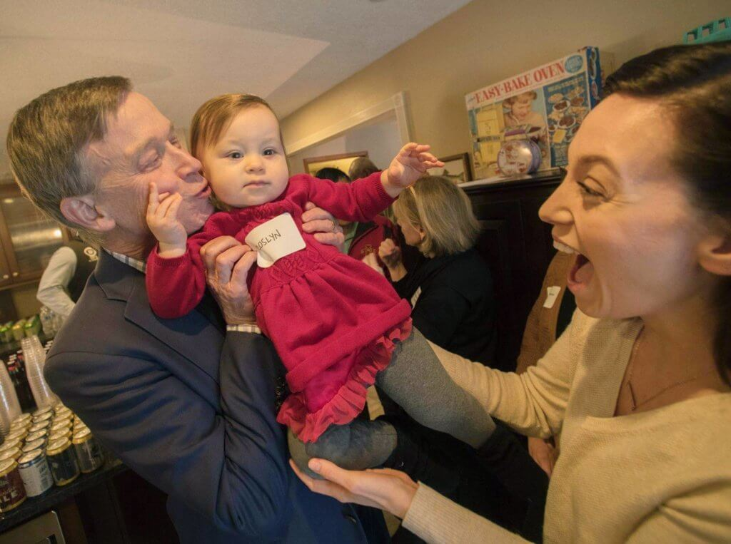 Former Colorado Gov. John Hickenlooper kisses Roslyn Vaughan while making a presidential campaign stop at a house party in Des Moines, Iowa on Jan. 27, 2019 (Photo by Evan Semón)