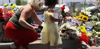 EL PASO, TEXAS - AUGUST 04: Jessica (L) and Kalani Windham leave flowers and a candle outside Walmart, near the scene of a mass shooting which left at least 20 people dead, on August 4, 2019 in El Paso, Texas. A 21-year-old male suspect, identified as Patrick Crusius from a Dallas suburb, surrendered to police at the scene. At least 26 people were wounded in the shooting. (Photo by Mario Tama/Getty Images)