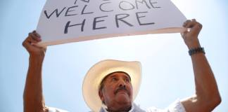EL PASO, TEXAS - AUGUST 07: Miguel de Anda, born and raised in El Paso, holds a sign reading 'Trump Not Welcome Here' at a protest against President Trump's visit following a mass shooting, which left at least 22 people dead. A 21-year-old white male suspect remains in custody in El Paso which sits along the U.S.-Mexico border. (Photo by Mario Tama/Getty Images)