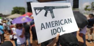 EL PASO, TEXAS - A demonstrator holds a sign depicting an assault rifle at a protest against President Trump's visit, following a mass shooting which left at least 22 people dead, on August 7, 2019. Protestors also called for gun control and denounced white supremacy. (Photo by Mario Tama/Getty Images)