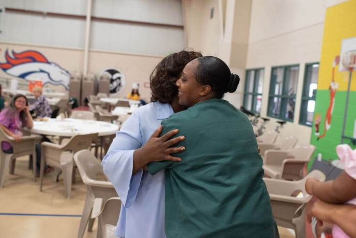 A prisoner embraces her mother at the start of the arts and education day at the Denver women's prison. (Photo by Annaleisa for the DU Prison Arts Initiative)