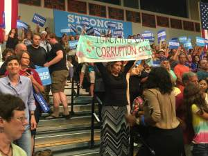 """Protester holding up sign on """"DNC corruption."""" It didn't last long - she was later escorted out by police."""