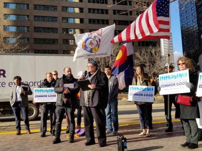 Representatives from Coloradans for the Common Good speak alongside members of the Colorado Carpenters' Union and workers before a hearing at the Colorado Department of Labor and Employment on a proposal to expand overtime protections on Dec. 16, 2019. (Photo by Forest Wilson)