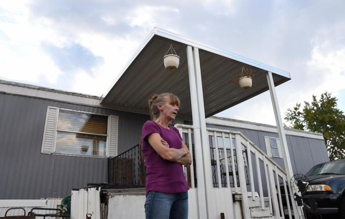Aug. 30, 2019 - Karla Lyons, outside her mobile home at the Lamplighter Village in Federal Heights, Colo. Lyons' waitressing wages are eaten up by a constant stream of home and yard repairs ordered by her park manager, including removal of a giant maple tree that fell on her patio roof and crushed it. She would move if she could afford it. (Kathryn Scott/The Colorado Sun)