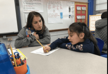 Denver Superintendent Susana Cordova leans down to watch a student work on math problems at Columbine Elementary. (Photo credit: Melanie Asmar/Chalkbeat)