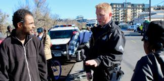 Denver Police Sgt. Brian Conover speaks with Dorian Phillips on Nov. 14, 2018, during a police sweep of a homeless encampment in Five Points. (Photo by Alex Burness for The Colorado Independent)