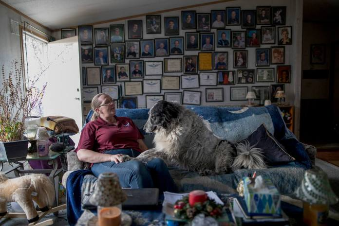 "In this March 30, 2018 photo Petra Bennett sits on the couch in her mobile home with her dog Romeo, in front of what she called her ""wall of fame,"" which was covered in photos of her three sons, all of whom grew up in the home, Residents of Denver Meadows Mobile Home and RV Park, including Petra Bennett, were forced to relocate after the land of the park was rezoned. (Philip B. Poston/Sentinel Colorado via AP)"