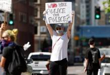 A demonstrator wears a face mask and latex gloves while waving a placard along Lincoln Avenue during a protest Tuesday, June 2, 2020, in Denver over the death of George Floyd, a handcuffed black man in police custody in Minneapolis. (David Zalubowski/AP)
