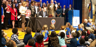 Dozens of Stedman Elementary kindergarteners look on as Gov. Jared Polis signs the full-day kindergarten bill into law on May 21, 2019. (Photo by Kati Weis/Chalkbeat Colorado)