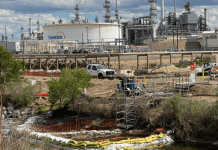 Suncor Energy contractors work along Sand Creek after the detection of a chemical sheen on the water outside the oil refinery north of Denver on Wednesday, May 27, 2020.
