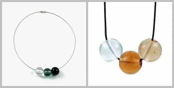 Drei runde Glasperlen in den Farben transparent, dunkelgruen und schwarz an einem Collier sowie drei weitere Glasperlen in den Farben eisblau, amber und hellbraun an einem schwarzen Kunstleder-Band.