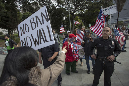 """A woman in a taupe coat stands before a uniformed police officer holding up a sign that says """"No ban, no wall."""""""