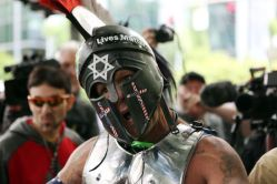 A white man wearing armor adorned with crosses made of American flags grimaces at a demonstration.