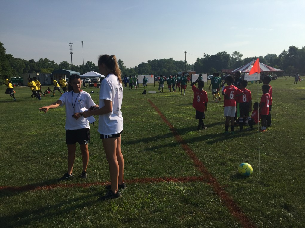 Lila Remache (left) and Hannah Sargent prepare to referee some under-10 4v4 soccer at the inaugural Columbus Nations Cup on July 14, 2018.