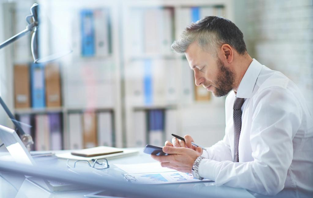 Image of office worker accessing his mobile device in office. Business Mobile Plans and Business Mobile Solutions from Columbus UK. Call 0333 240 7755 for further information.