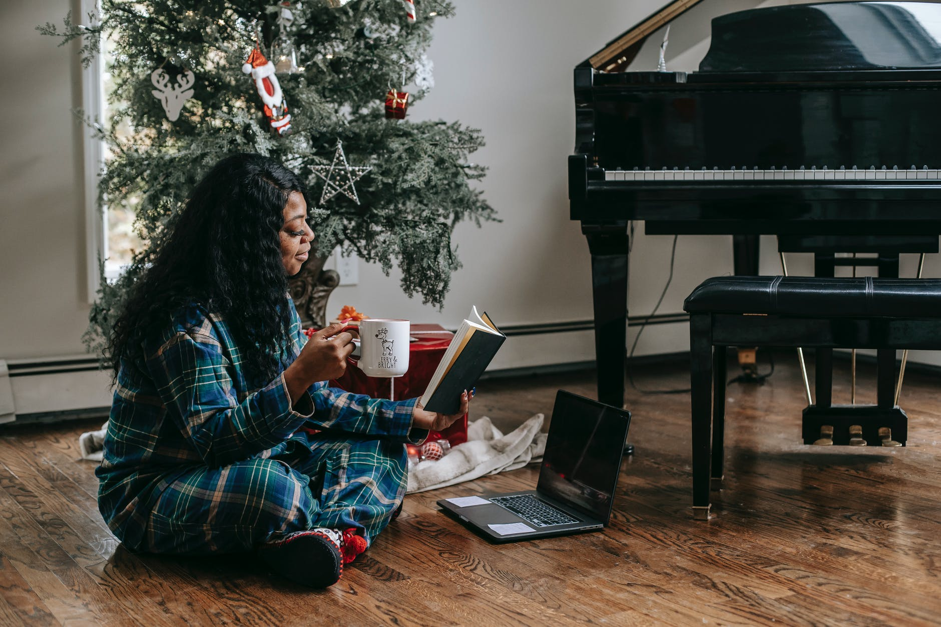 black woman reading book near laptop and christmas tree